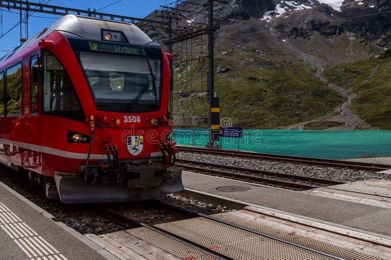 Czerwony RhB pociąg w Ospizio Bernina staci kolejowej, Grisons, Szwajcaria fotografia royalty free