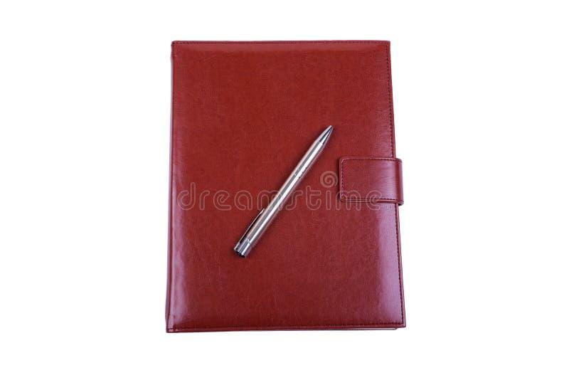 Czerwony rzemienny dzienniczek i balowy pióro odizolowywający na bielu zdjęcie royalty free