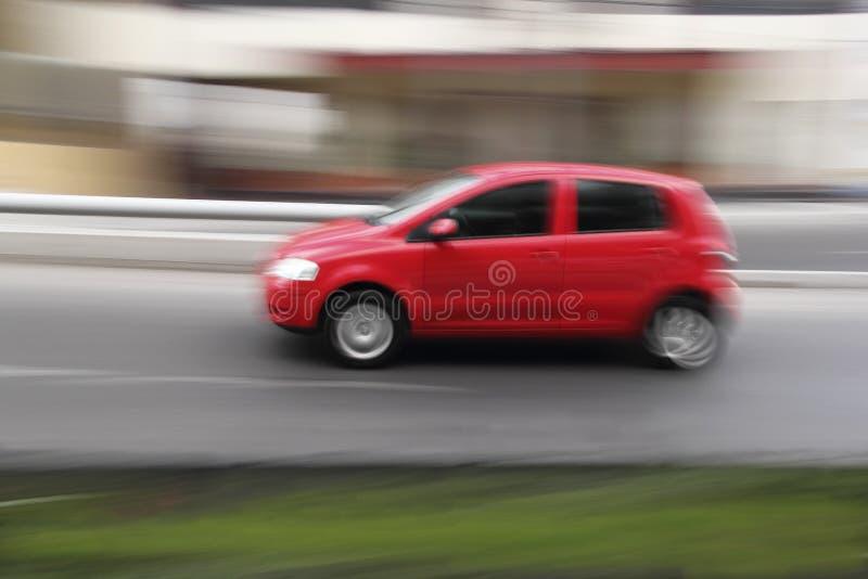 Czerwony samochód przy miasto ulicą. zdjęcie stock