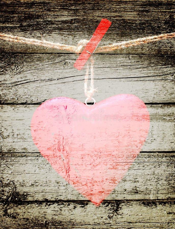 Czerwony serce na arkanie na grunge drewnianym tle obrazy royalty free