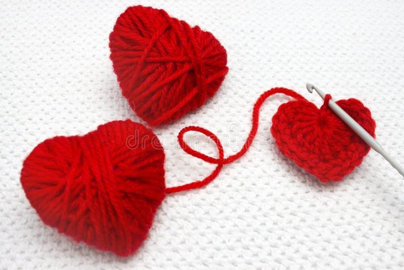 Czerwony serce robić wełny przędza i szydełkowy serce miękkie ogniska, Handmade szydełkujący wełny organicznie czerwony serce Sta obraz stock