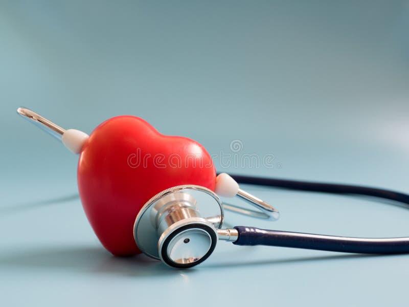 Czerwony serce używa głębokiego błękitnego stetoskop na błękitnym tle dla słucha ich swój serce Pojęcie miłość i troskliwy pacjen obrazy royalty free