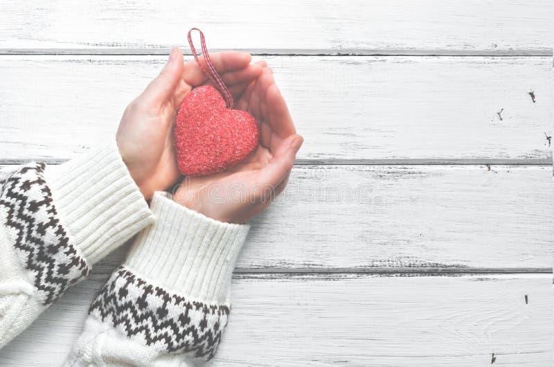 Czerwony serce w rękach młoda kobieta w białym wełna pulowerze z ornamentem na białym drewnianym nieociosanym tle Walentynki ` s fotografia stock