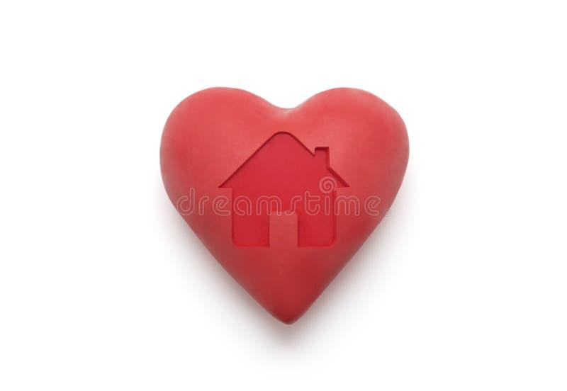 Czerwony serce z imprinted domowym kształtem nad białym tłem fotografia stock