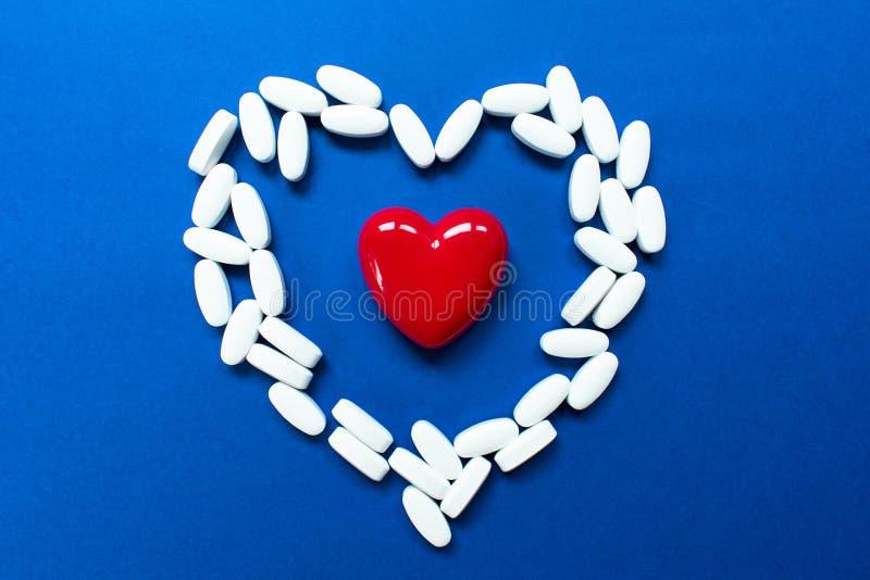Czerwony serce z pigułkami na błękitnym tle fotografia stock