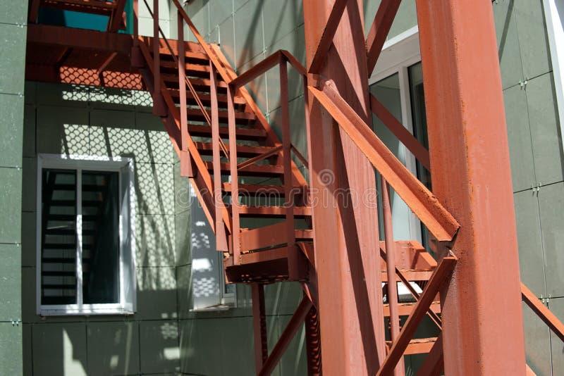 Czerwony stalowy schody zieloną ścianą zdjęcie stock