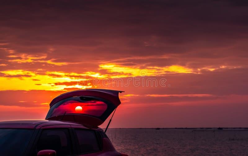 Czerwony SUV samochód z sporta projektem z otwartą samochód ciężarówką parkującą na betonowej drodze morzem przy zmierzchu niebem fotografia royalty free