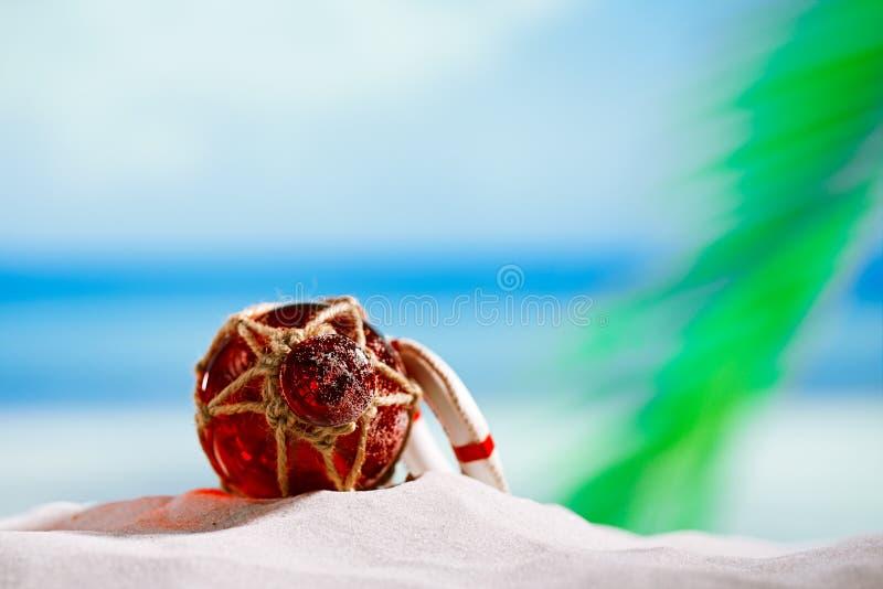 Czerwony szkło pławik na plażowym piasku i dennym błękitnym tle fotografia royalty free