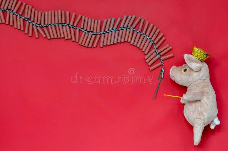 Czerwony tło trzyma zapałczanego świniowata lala przygotowywa zaświecać petardy zdjęcie stock