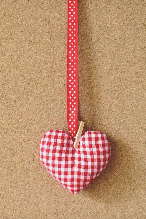 Czerwony tekstylny serce nad brown rzemiosłem przetwarza korka deskowego tło Walentynki ` s dnia pojęcie obraz royalty free