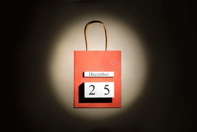 Czerwony torba na zakupy z bożymi narodzeniami 25 Grudzień data w promieniu scenicznego punktu światło nad ciemnym tłem zdjęcie stock