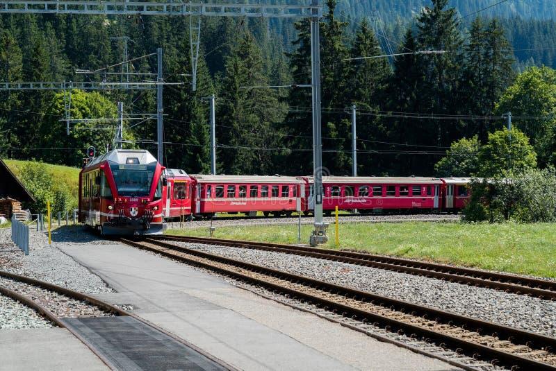 Czerwony wąskiego wymiernika pociąg przyjeżdża przy dalekim dworcem w Szwajcarskich Alps obraz royalty free