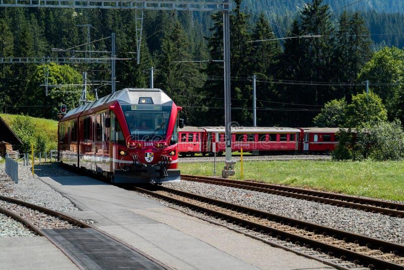 Czerwony wąskiego wymiernika pociąg przyjeżdża przy dalekim dworcem w Szwajcarskich Alps obrazy royalty free