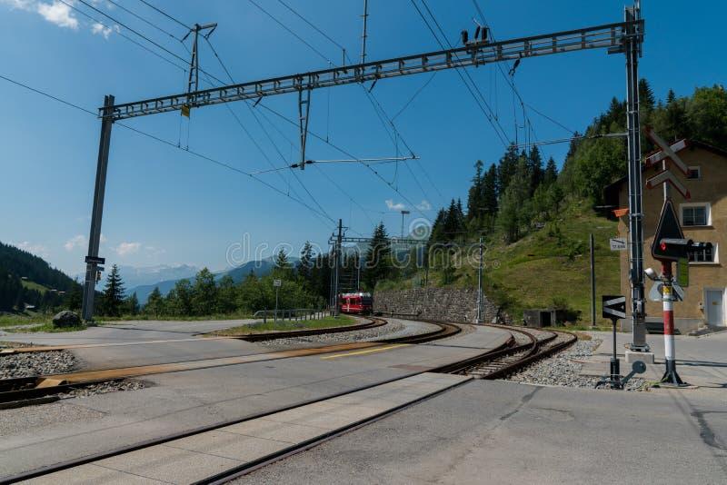 Czerwony wąskiego wymiernika pociąg przyjeżdża przy dalekim dworcem w Szwajcarskich Alps fotografia stock