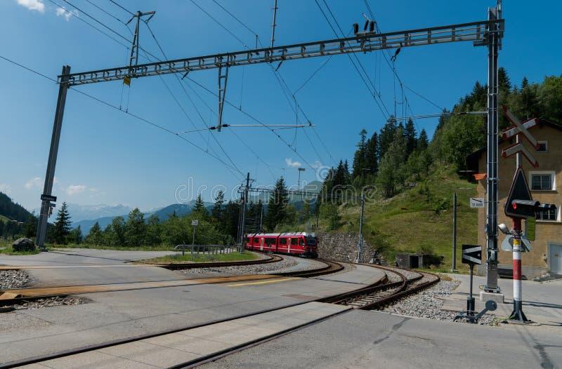 Czerwony wąskiego wymiernika pociąg przyjeżdża przy dalekim dworcem w Szwajcarskich Alps fotografia royalty free