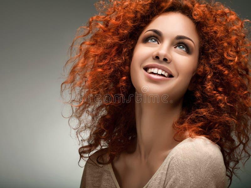 Czerwony włosy. Piękna kobieta z Kędzierzawy Długie Włosy. zdjęcia royalty free