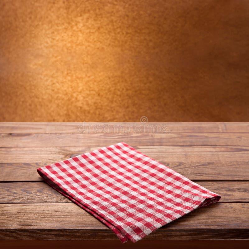 Czerwony w kratkę tablecloth na drewnianym stole Pielucha odgórnego widoku zamknięty up egzamin próbny up zdjęcie stock
