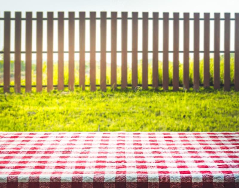 Czerwony w kratkę tablecloth tekstury wierzchołek z widoku ogródem, ogrodzenie obrazy royalty free
