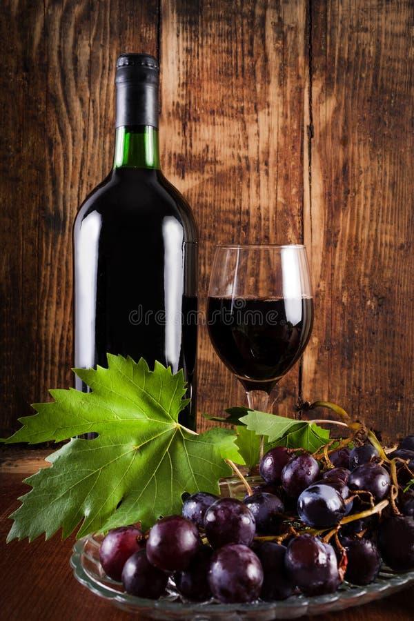 Czerwony winogrono na talerzu z winograd dekoracją, szkło i butelka czerwone wino zdjęcia stock