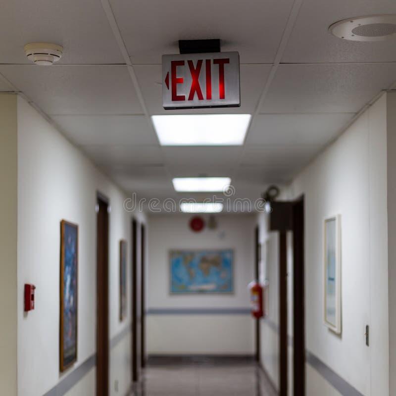 czerwony wyjście ewakuacyjne podpisuje wewnątrz ciemnego pokój iluminujący biurowy wyjście znak fotografia stock