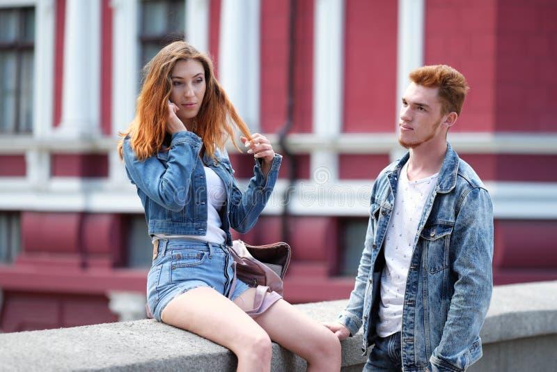 Czerwony z włosami facet czeka czerwonej z włosami dziewczyny opowiada na jej telefonie komórkowym obraz royalty free