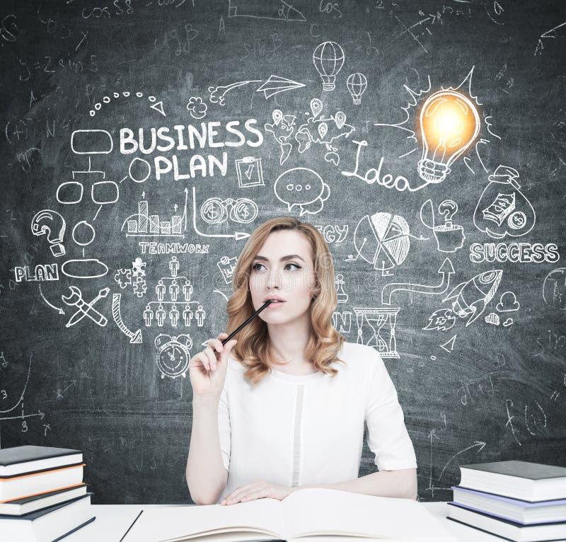 Czerwony z włosami uczeń przy stołem, plan biznesowy obrazy stock