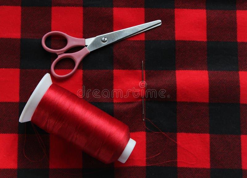 Czerwony zagrożenie z igłą i nożycami na kolorowej tkaninie Widoku abo obrazy stock