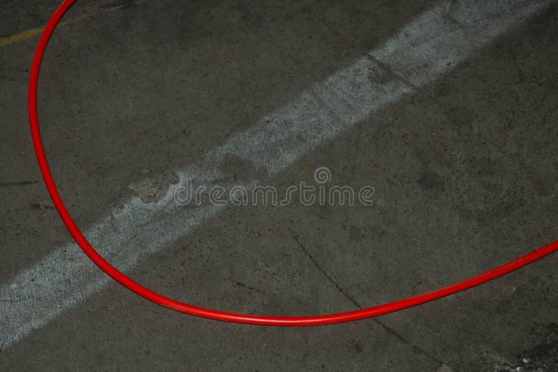 Czerwony zasilanie elektryczne kabel czerwień drut kłama na ziemi bałagan na cementowej podłodze zdjęcie stock