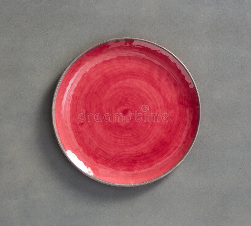 Czerwony zawijasa Melamine talerz z zmrokiem - szary tło zdjęcie stock