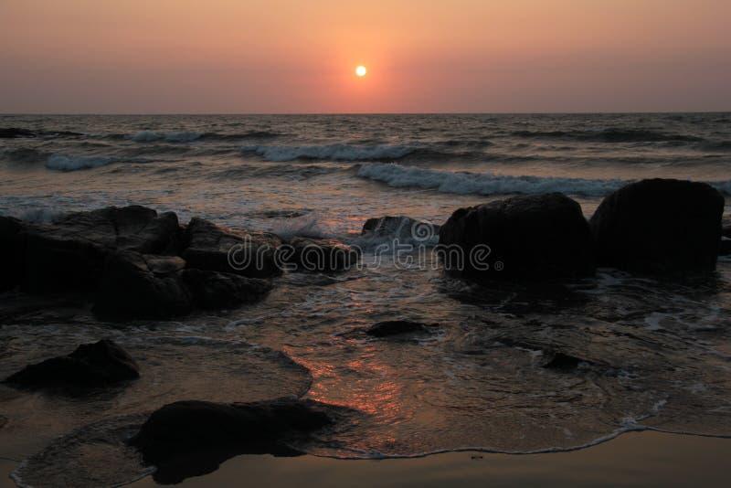 Czerwony zmierzch w koszcie z kamieniami ocean fotografia stock