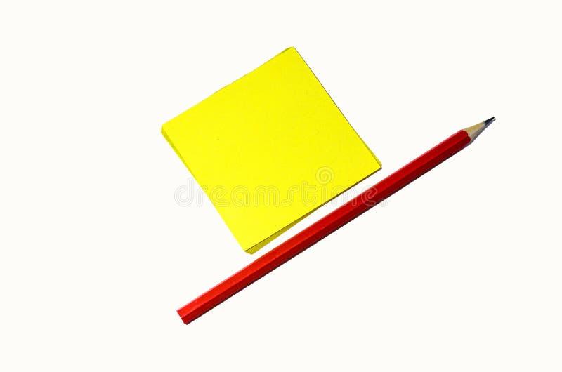 Czerwony zwyczajny ołówek i kawałek kwadratowy koloru żółtego papier dla pisać kłamstwie na białym tle zdjęcie royalty free