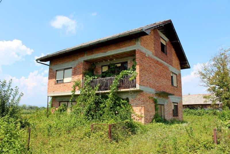Czerwonych cegieł rodziny porzucający dom z łamanymi okno i frontowym drucianym ogrodzeniem przerastającymi z wysokimi uncut rośl fotografia royalty free