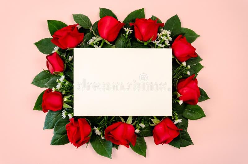 Czerwonych róż bukiet z pustą białej księgi kartą na pastelowych menchii tle zdjęcie stock