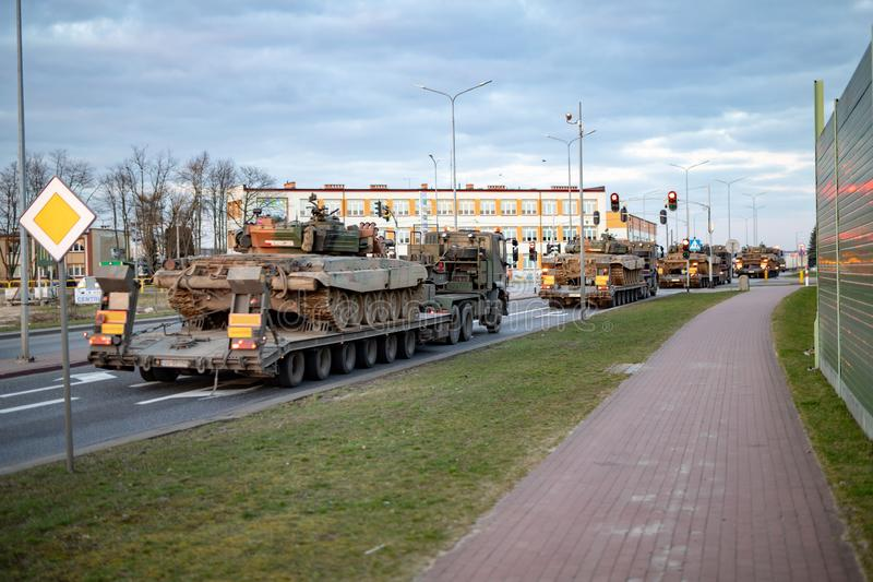 Czluchow, pomorskie / Poland - March, 22, 2019:. Transport of tanks on a carriage in normal city traffic. Supplying military royalty free stock image