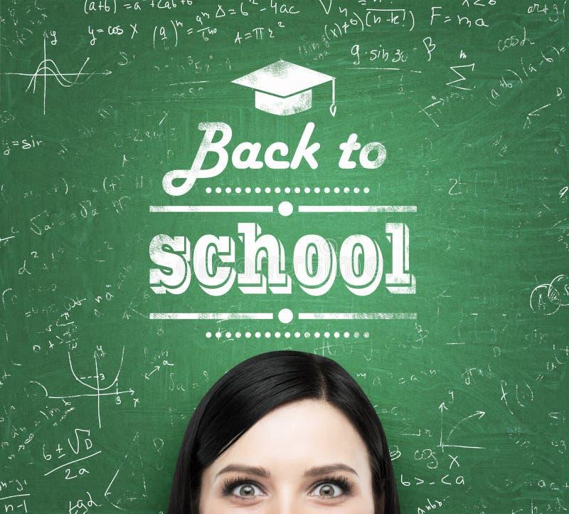 Czoło słowa i dziewczyna: 'z powrotem szkoła' które napiszą na zielonym chalkboard zdjęcia stock