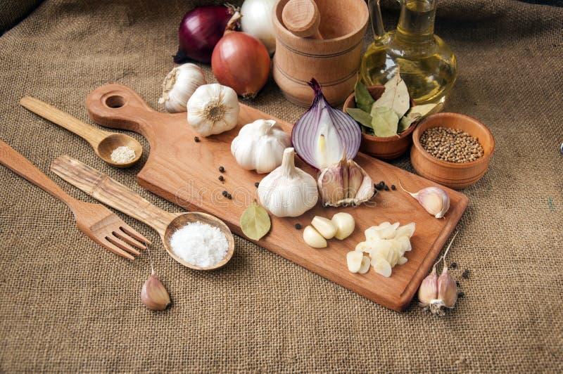 Czosnek, cebula, kolender, sezamowi ziarna, czarny pieprz, podpalany liść, morze sól, oliwa z oliwek fotografia stock