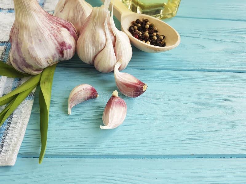 Czosnek, czarny pieprz, nafciany odżywiania aromaticon błękita drewno obraz royalty free