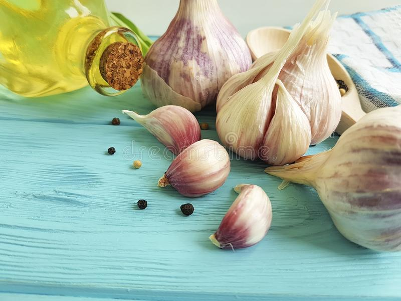 Czosnek, czarny pieprz, przyprawowy wieśniaka kucharza stołu oleju odżywiania aromaticon błękita drewno zdjęcie royalty free