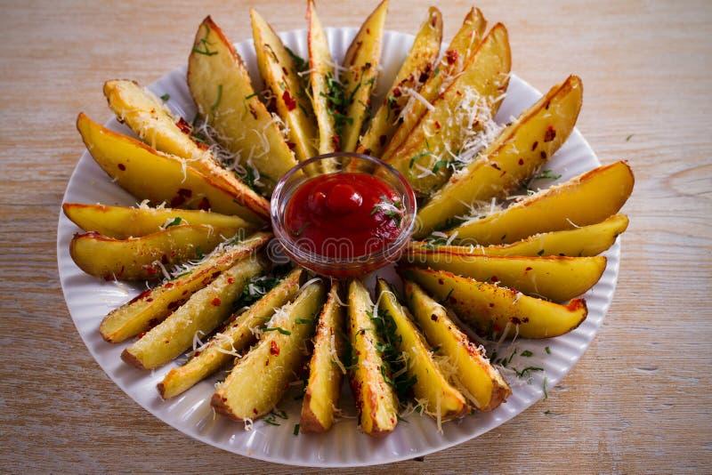 Czosnek piec kartoflanych kliny z papryki i parmesan serem Grula dłoniaki na bielu talerzu zdjęcie royalty free