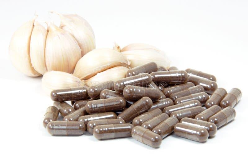 Czosnek ziołowe kapsuły, oralna medycyna, alternatywna medycyna odizolowywająca na białym tle. zdjęcie stock