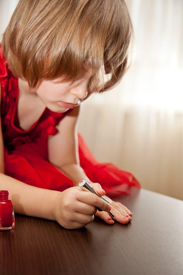 Mała dziewczynka w czerwonej sukni malował gwoździe z gwoździa połyskiem zdjęcia stock