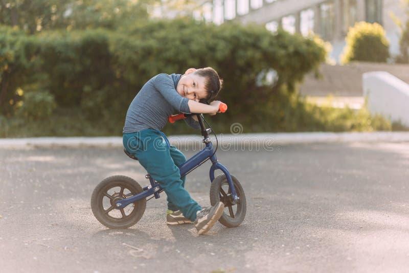Czteroletnia rozochocona ch?opiec siedzi na dzia?aj?cym rowerze i patrzeje kamer? w sneakers Dzieci i sporty obrazy stock