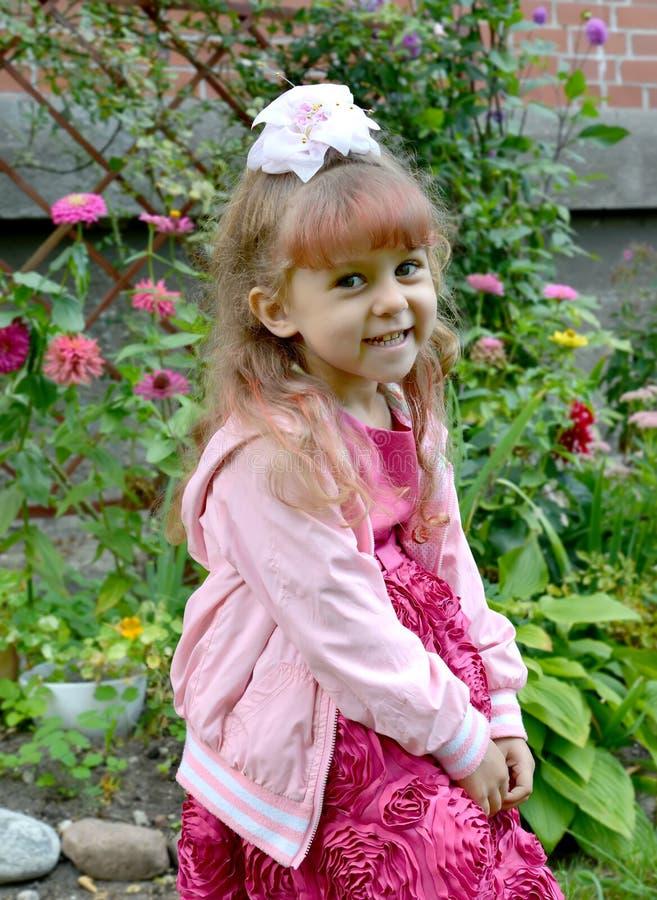 Czteroletnia rozochocona dziewczyna w ogródzie przeciw tłu kwiaty obraz stock