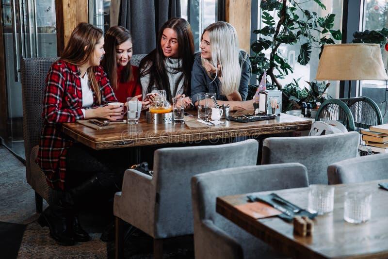 Cztery żeńskiego przyjaciela cieszy się w opowiadać przy kawiarnią obrazy stock