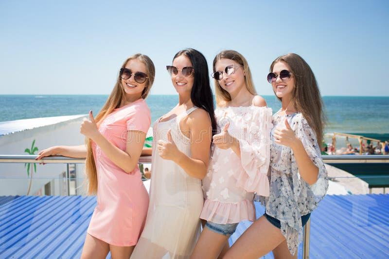 Cztery atrakcyjnej młodej kobiety stoi na kurortu tle Uśmiechnięte damy w przypadkowych ubraniach i słońc szkłach Dziewczyny dale fotografia stock