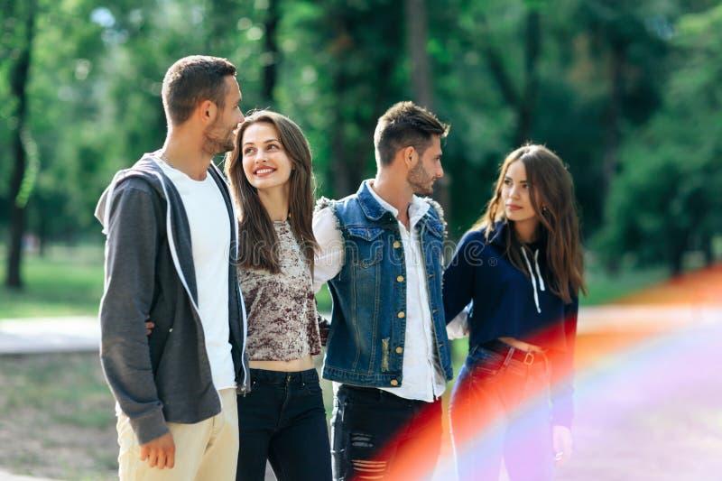 Cztery beztroskiego młodzi ludzie chodzi w parku na słonecznym dniu zdjęcie royalty free