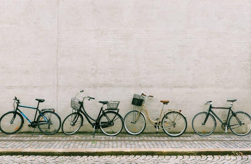 Cztery bicykli/lów stojak blisko białej ściany z cegieł zdjęcie stock
