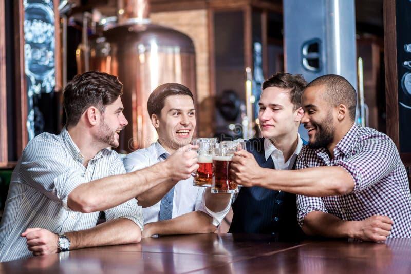 Cztery biznesmena piją piwo i radują się wpólnie przy barem Suc obrazy stock