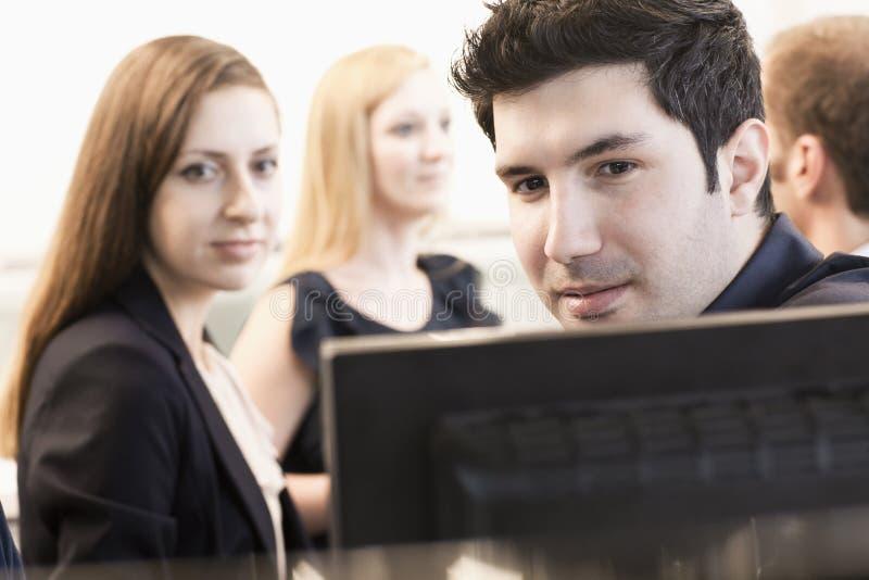 Cztery coworkers siedzi i dyskutuje w biurze komputerowymi monitorami obraz royalty free
