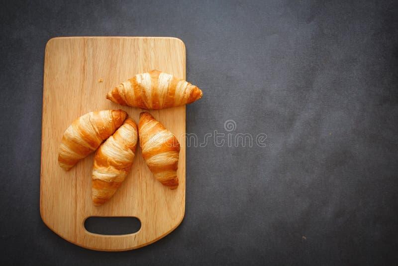 Cztery croissants na drewnianej lekkiej tnącej desce na ciemnym rzemiośle tapetują obraz royalty free